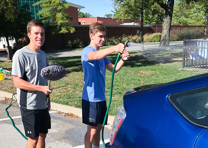 Jack and Jeremy washing a blue car